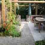 Lange zichtlijn vanuit woonhuis door tuin- compacte stadstuin met open haard en eten uit eigen tuin.