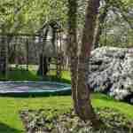 tuin met speelruimte voor kinderen, harmonieus opgenomen in geheel.