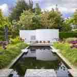 Moderne strakke achtertuin met spiegelvijver en bloei van allium bollen in siergrassen.