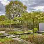 stoere strakke moderne tuin met koi vijver en terrassen