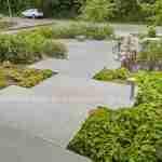 Grote betonnen stenen als toegangspad in een voortuin met hoogteverschil
